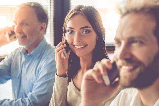 Hermosas personas de negocios están hablando por los teléfonos móviles.