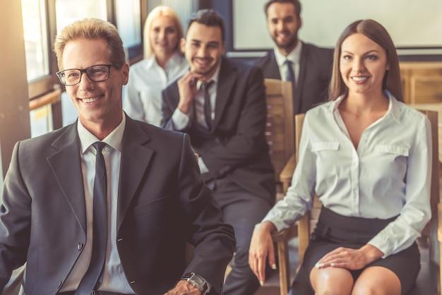 Hermosas personas de negocios en ropa formal están sonriendo
