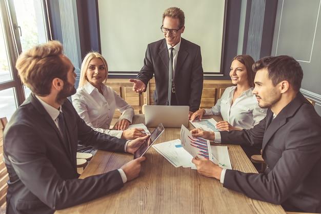 Hermosas personas de negocios en trajes están discutiendo asuntos