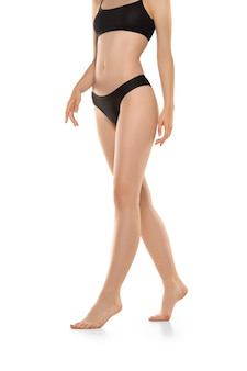 Hermosas piernas femeninas, caderas y vientre aislado en la pared blanca, belleza