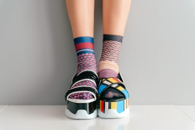 Hermosas piernas femeninas en coloridos calcetines y sandalias no coincidentes
