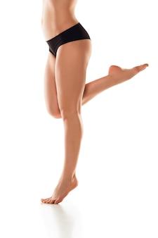 Hermosas piernas femeninas, glúteos y vientre aislados en la pared blanca. concepto de belleza, cosmética, spa, depilación, tratamiento y fitness. cuerpo en forma y deportivo, sensual con piel cuidada en ropa interior.