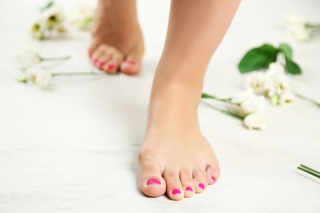 Hermosas piernas femeninas en piso blanco