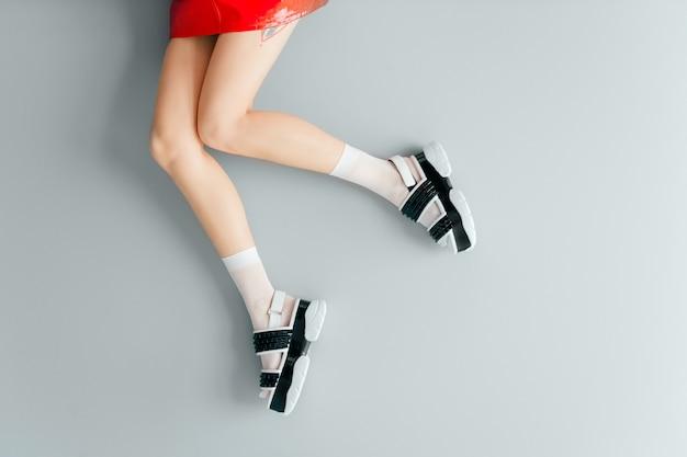 Hermosas piernas femeninas en sandalias de moda y medias blancas