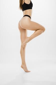 Hermosas piernas femeninas y vientre aislado sobre fondo blanco, belleza, cosméticos, spa, depilación