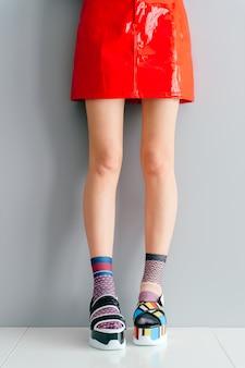 Hermosas piernas femeninas en zapatos de moda y calcetines coloridos