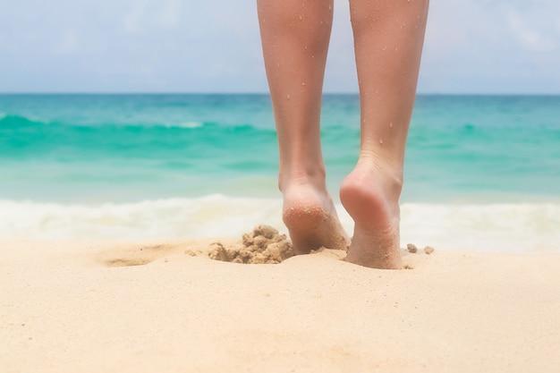Hermosas piernas suaves de las mujeres en la playa de arena blanca