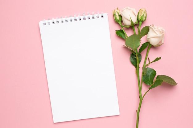 Hermosas rosas blancas flor y cuaderno sobre fondo rosa