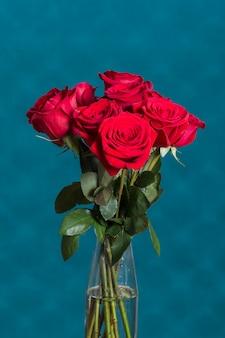 Hermosas rosas en florero delante de la pared azul