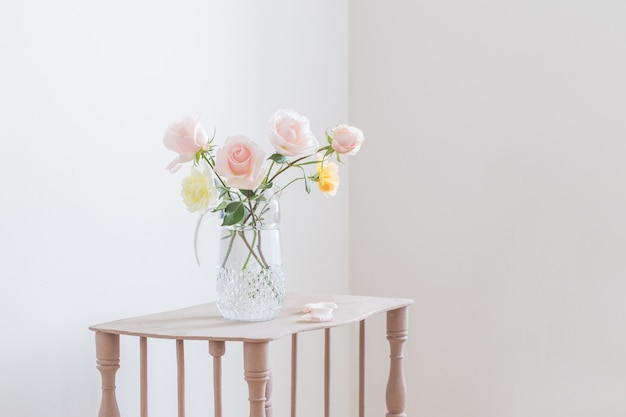 Hermosas rosas en jarra de vidrio sobre fondo blanco.
