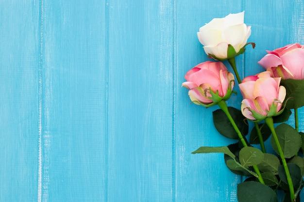 Hermosas rosas en madera azul con ritmo de copys