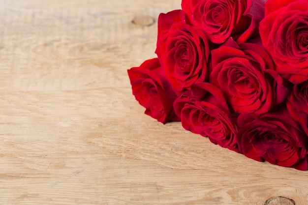Hermosas rosas en mesa de madera