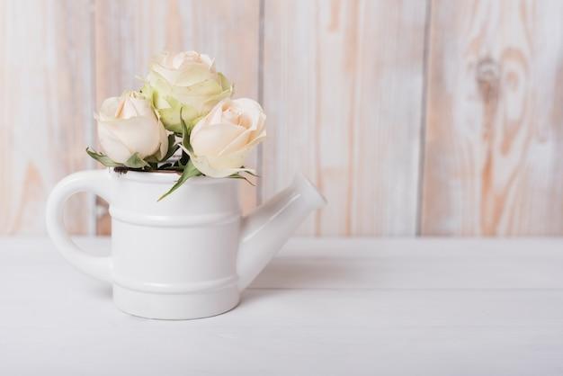 Hermosas rosas en la pequeña regadera de cerámica en mesa de madera.