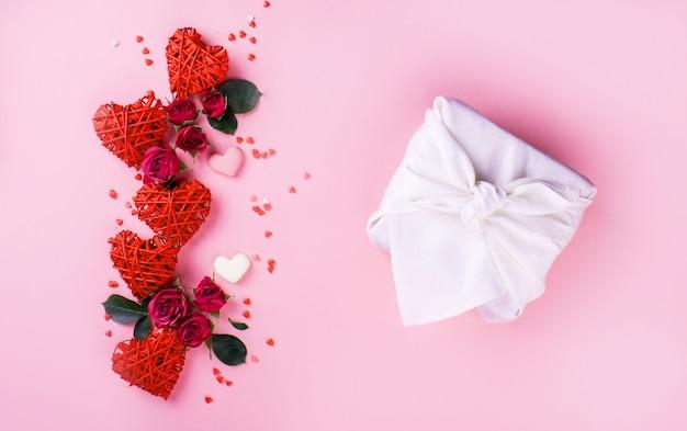 Hermosas rosas pequeñas, corazones pequeños, corazones de chocolate con leche, sobre un fondo rosa con un hermoso regalo de foroshik con color blanco.