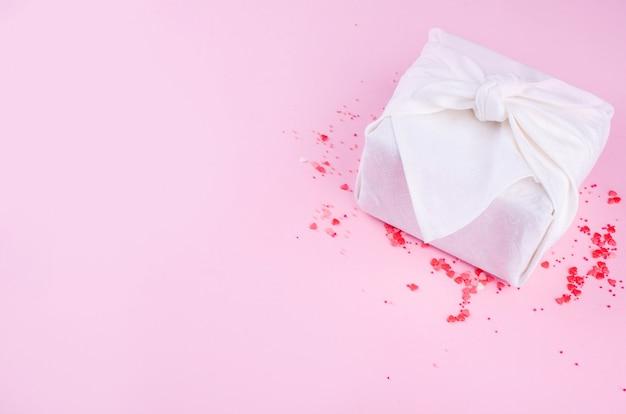 Hermosas rosas pequeñas, corazones pequeños, corazones de chocolate con leche, sobre un fondo rosa con un hermoso regalo de furoshik con color blanco.