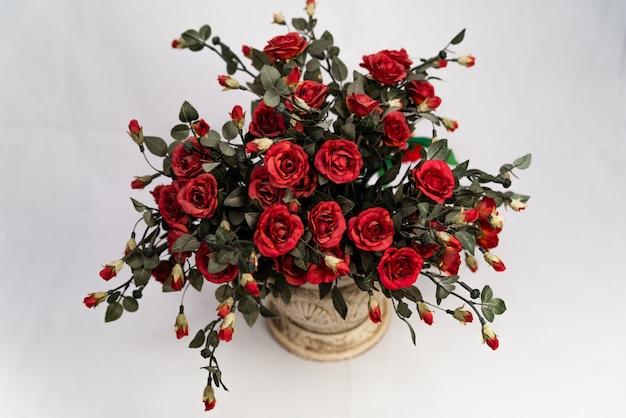 Hermosas rosas rojas en una maceta de cerámica