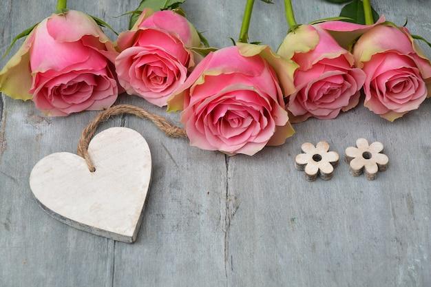 Hermosas rosas rosadas con un corazón de madera y florecitas sobre una superficie de madera