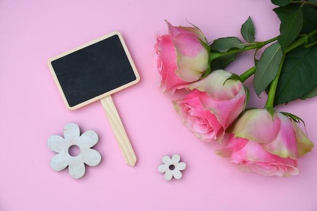 Hermosas rosas rosadas con pequeñas flores en forma de madera sobre una superficie rosa