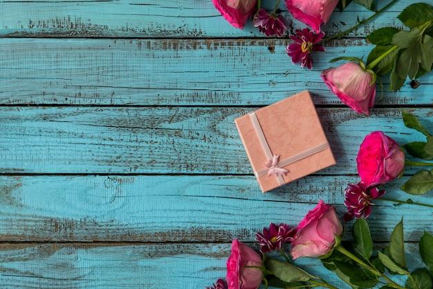 Hermosas rosas rosadas y pequeño regalo.