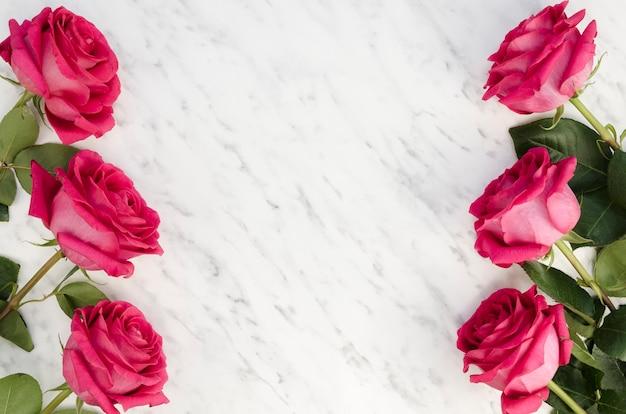 Hermosas rosas rosadas sobre fondo de mármol