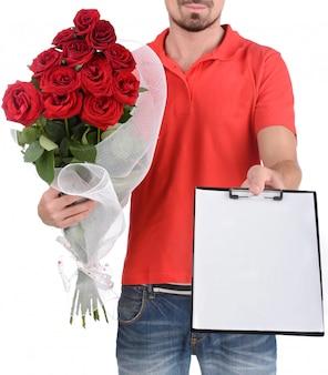 Hermosas rosas para ti! repartidor sosteniendo una rosas rojas.