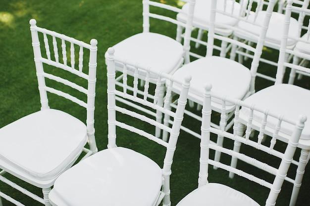 Hermosas sillas de boda blancas en la ceremonia en el parque.