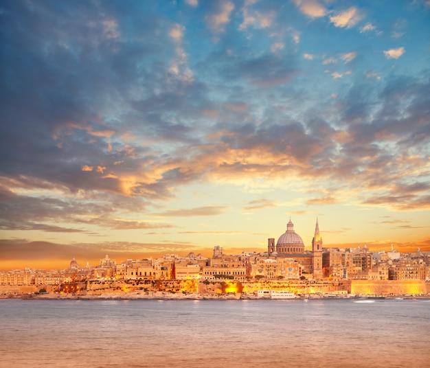 Hermosas torres y la cúpula de la catedral de la valeta bajo un cielo dramático en la puesta del sol