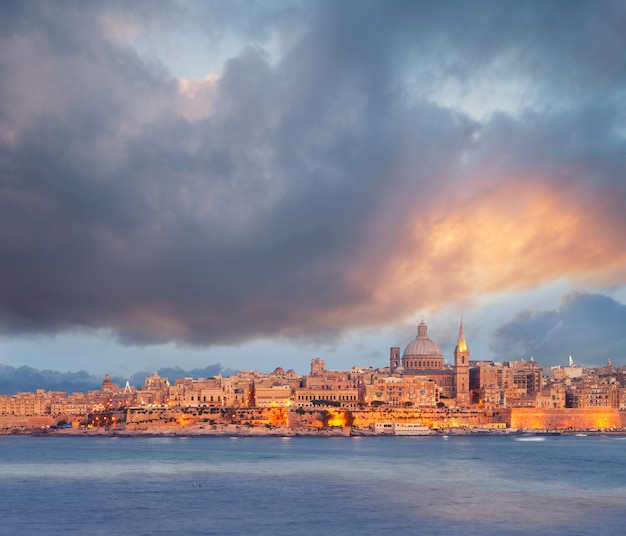 Hermosas torres y cúpula de la catedral de la valeta bajo el cielo dramático en la puesta del sol