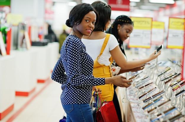 Hermosas tres clientes afroamericanas bien vestidas con bolsas de colores en la tienda de telefonía móvil que eligen teléfono inteligente.