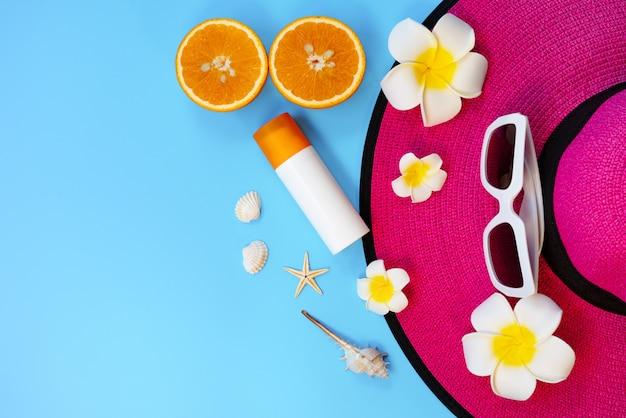 Hermosas vacaciones de verano, accesorios de playa, gafas de sol, gorro, naranja, bloqueador solar y conchas.