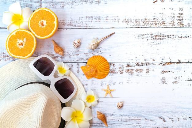 Hermosas vacaciones de verano, accesorios de playa, naranja, gafas de sol, sombrero y conchas.