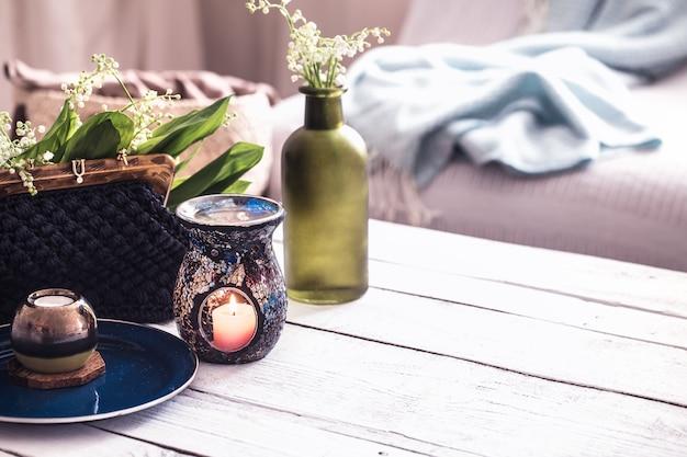 Hermosas velas encendidas con hojas verdes en el bolso sobre la mesa blanca