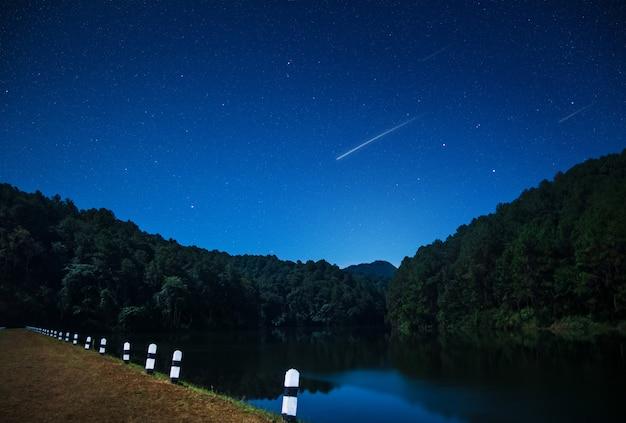 Hermosas vistas de la naturaleza en la noche con una estrella fugaz en la presa del norte de tailandia.