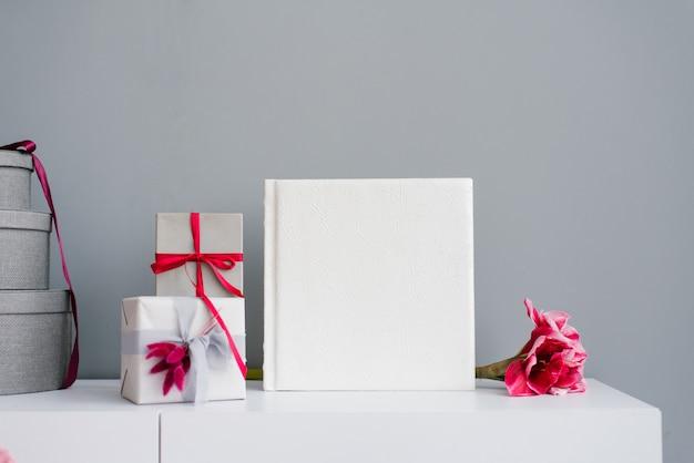 Hermoso álbum de fotos de boda en cuero con encaje en relieve rodeado de cajas de regalo
