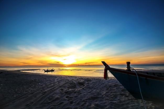 Hermoso amanecer al atardecer en la playa con bote silueta