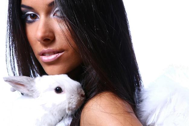 Hermoso ángel con conejito blanco