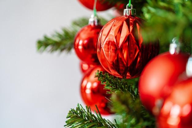 Hermoso árbol de navidad con adornos rojos de cerca