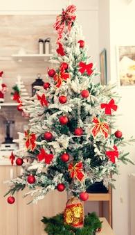 Hermoso árbol de navidad decorado en la cocina vacía