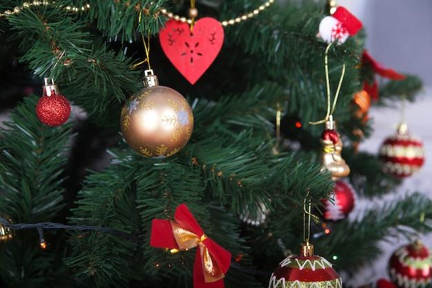 Hermoso árbol de navidad verde con bolas doradas y rojas