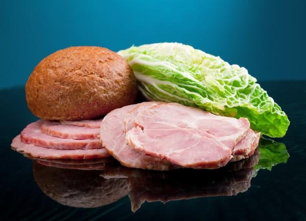 Hermoso arreglo de alimentos en rodajas de carne, pan y verduras