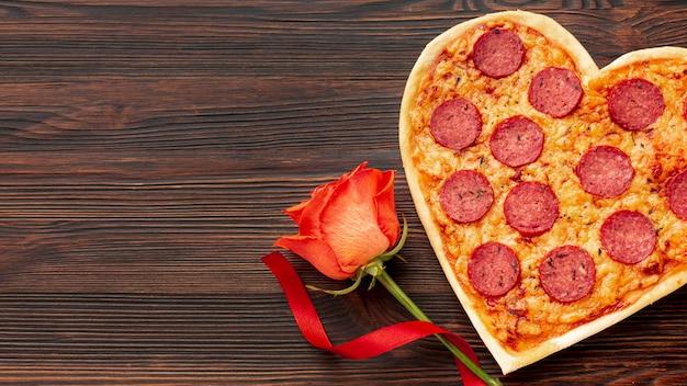 Hermoso arreglo para la cena del día de san valentín con pizza en forma de corazón y rosa