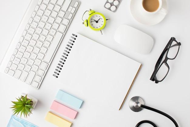 Hermoso arreglo del escritorio de la clínica con taza de café y reloj despertador