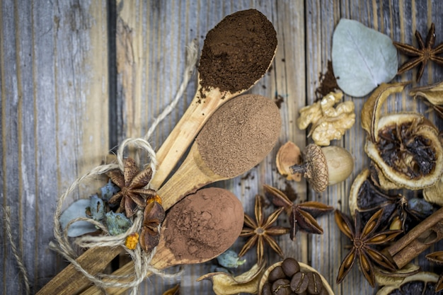 Un hermoso arreglo de limones secos, canela, café en cucharas de madera sobre madera.