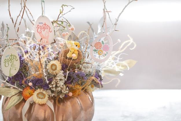 Un hermoso arreglo de pascua con flores y huevos.