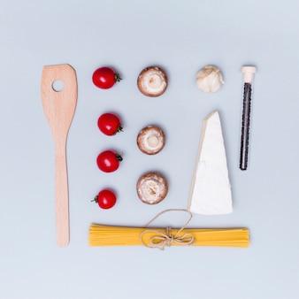 Hermoso arreglo de pasta cruda de espagueti y su ingrediente con espátula de madera