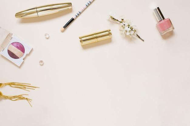 Hermoso arreglo plano con flores de manzana, cosméticos y otros accesorios. maqueta de blogger creativo o de belleza, fondo beige, espacio de copia