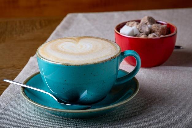 Hermoso arte latte delicioso, taza de café azul con azúcar morena sobre fondo brillante.