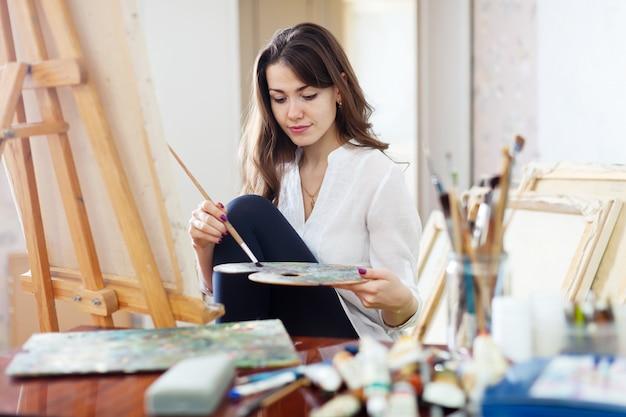 Hermoso artista pinta sobre lienzo