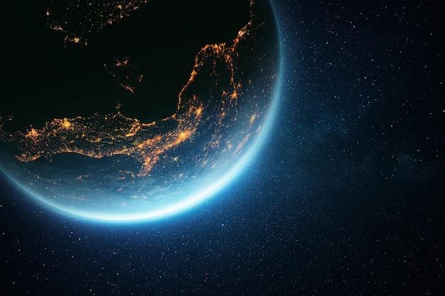Hermoso y asombroso planeta tierra con un resplandor azul y luces de la ciudad por la noche en el espacio ultraterrestre. concepto de humanidad y vida
