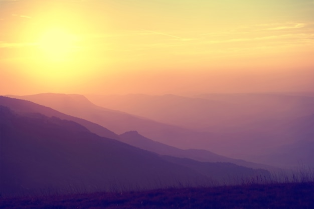 Hermoso atardecer en las montañas. paisaje colorido con sol y cielo naranja. coloreado como instagram